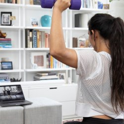 woman working out from home with dumbbells